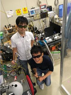 実験装置をバックにレーザー保護眼鏡をかけた状態でのスナップショット(武田:左、宇佐見:右)